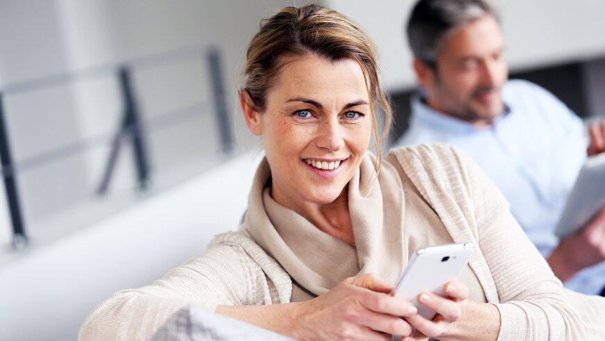 Hymyilevä nainen puhelin kädessä
